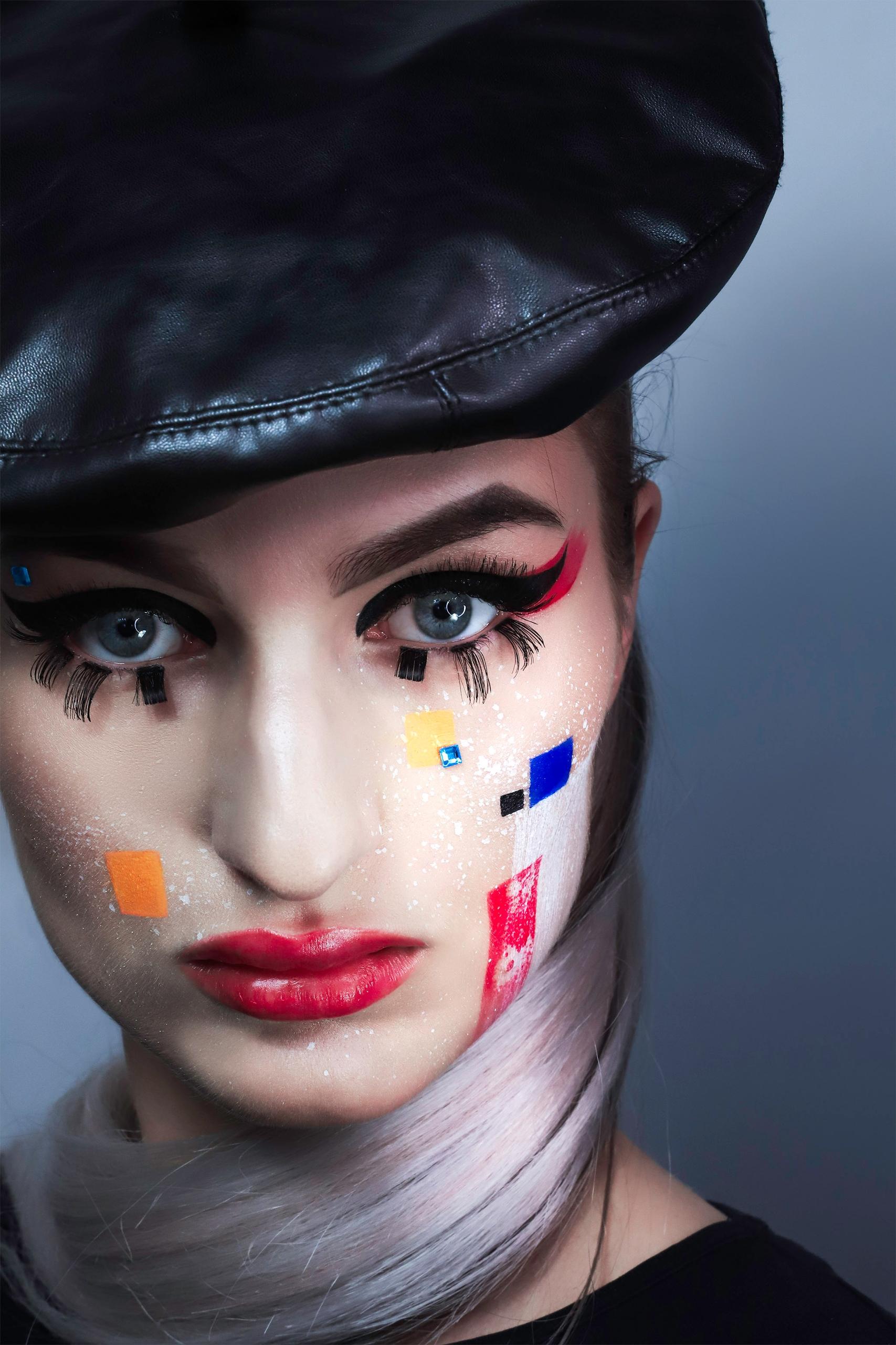 Zdjęcie przedstawia portret kobiety w kolorowym makijażu. Kobieta ma na sobie czarną bluzkę i beret.