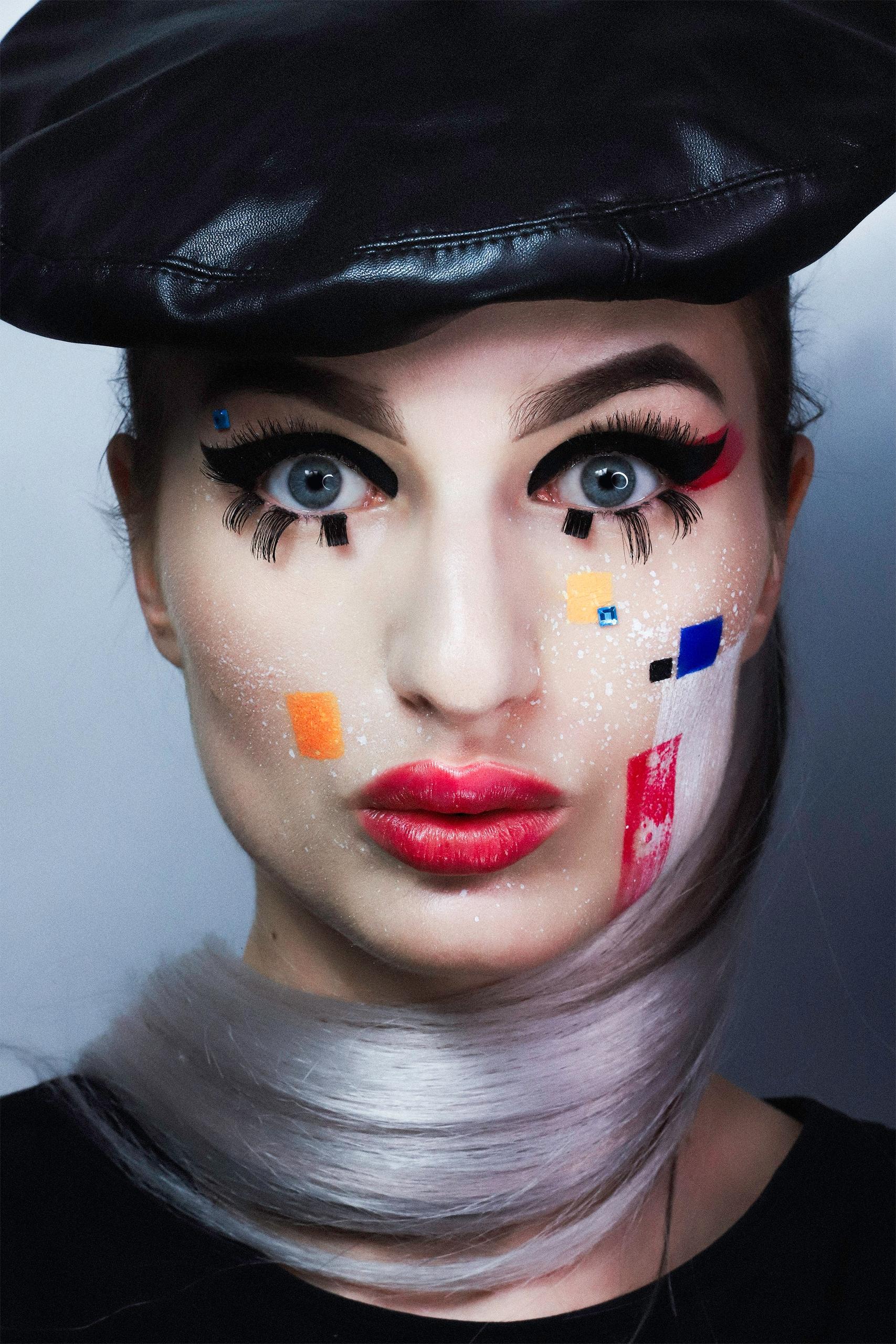 Fotografia przedstawia portret kobiety w kolorowym makijażu i czarnym skórzanym berecie.
